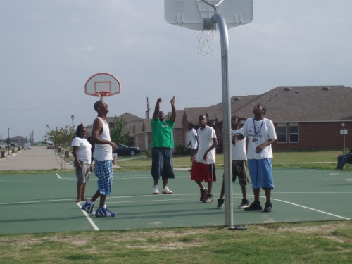 Kids playing basketball while waiting for crawfish