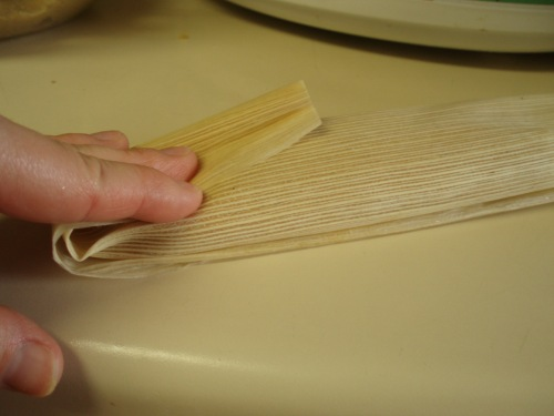 Folding the rolled-up corn husk